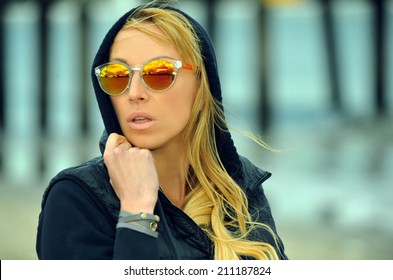 Portrait of fashionable young woman wearing jacket and sunglasses posing outside.