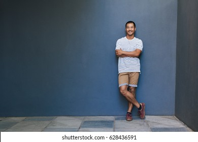 Portrait of a fashionably dressed smiling young Asian man leaning with his arms crossed against a gray wall outside