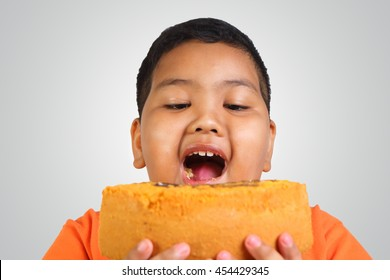 Portrait of a fat Asian boy eating big piece of cake