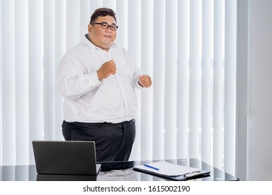 Portrait of fat Asian businessman wearing formal attire while cheering & dancing for his finished work in his office