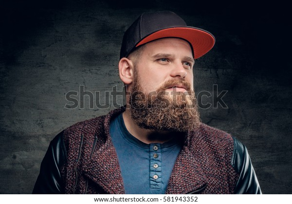 Portrait of fat bearded male dressed in a jacket and baseball cap.