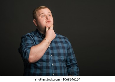 Portrait of Fat caucasian man thinking and looking up to copyspace
