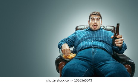 Portrait of fat caucasian man wearing jeanse and whirt sitting in a brown armchair isolated on gradient grey background. Watching TV drinks beer, eats chips and changing channels. Overweight, carefree