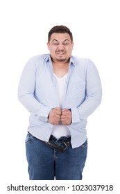 A portrait of a fat man suffers, trying to wear the shirt and close it, isolated on a white background.