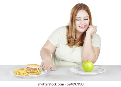 Portrait of fat woman chooses green apple while refuses hamburger and french fries, isolated on white background