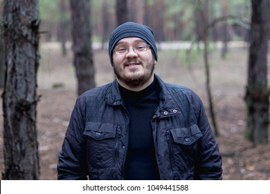 Portrait of a fat young man in a pine forest.