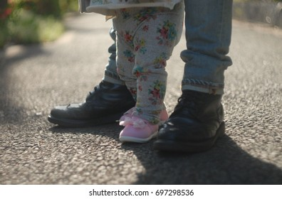 Portrait of father and baby legs. First steps. Outdoor