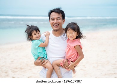 portrait a father carries his two daughter smile look at camera when walking around seashore