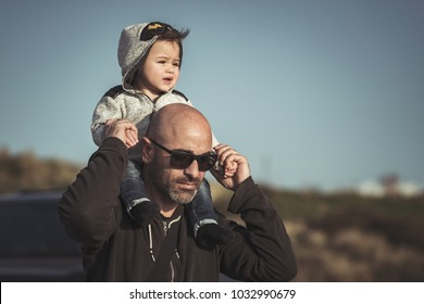 Portrait of a father carrying his cute little son on shoulders, baby and dad with pleasure spending time together outdoors, happy family life
