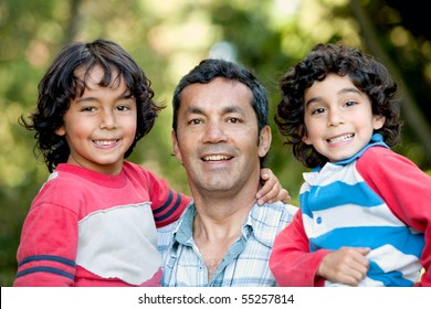 Portrait of a father carrying his sons outdoors and smiling