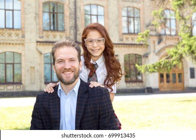 Portrait of father and daughter against the background of the school building.