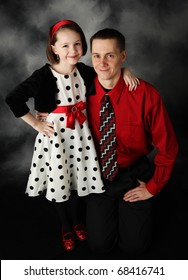 Portrait of father and daughter dressed up in red, black, and white hugging