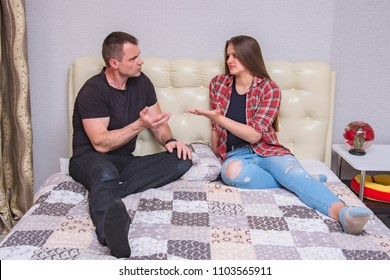 portrait of the father and daughter with family problems, family difficulties in family relationships in the room on the bed. They are right in front of the camera and look unhappy
