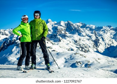 Portrait of father and daughter in green jacket skiing in French Alps on sunny winter day, Tignes.