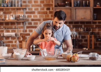 'portrait of father and daughter making cookies in kitchen