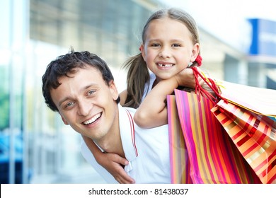 Portrait of father with daughter and shopping bags on back