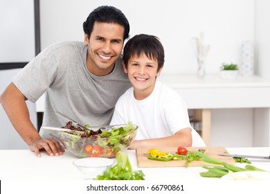 Portrait of a father and his son preparing a salad in the kitchen