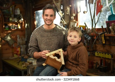 Portrait of a father and his son sitting on a table in a traditional wooden workshop. They are smiling, looking at camera while holding a wooden bird house, they built together.