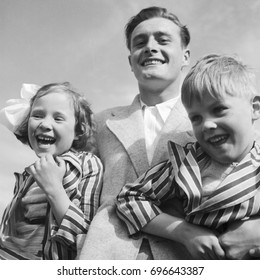 Portrait of father holding son and daughter