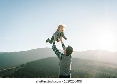 Porträt eines Vaters hält, wirft glückliche Tochter auf Hände, die im Herbst auf die Natur gehen. Papa und Kind spielen in den Bergen. Konzept des Familienvergnügens, Zeit zusammen im Urlaub zu verbringen.