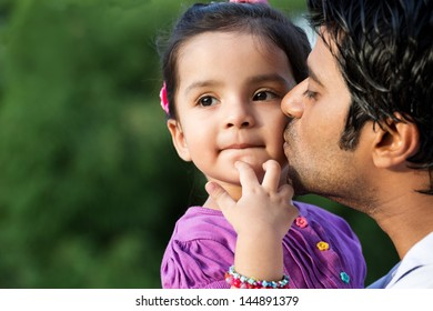 portrait if father kissing daughter in out door against nature background, Indian man kissing his daughter.