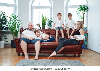 Portrait of father and mother in relationship with their children they sit on sofa and pose on camera in living room.