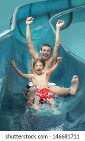 Portrait of father and son with arms outstretched on water slide