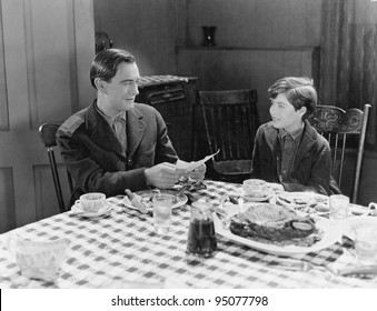 Portrait of father and son at dinner table