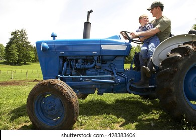 Portrait of father and son driving a tractor