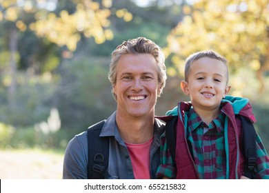 Portrait of father and son hiking in forest