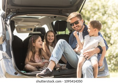 Portrait of father and three kids sitting in car trunk