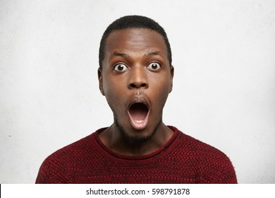 Portrait of fearful bug-eyed young African American man in casual sweater screaming in shock, keeping mouth wide open, feeling stressed after having forgotten to pay bills in time. Horizontal
