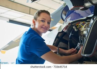Portrait Of Female Aero Engineer Working On Helicopter In Hangar