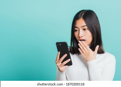 Portrait weiblich ängstlich auf dem Telefon sehen schlechte Nachrichten, Junge schöne asiatische Frau überrascht mit Handy Nahaufnahme mit Handy mit Handy, Studioaufnahme einzeln auf blauem Hintergrund