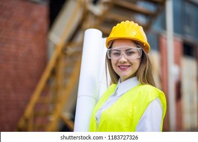 Portrait of female architect wearing hardhat and reflective vest