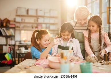 Portrait of female art teacher working with little girls in pottery class, scene lit by serene sunlight, copy space