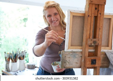 Portrait Of Female Artist Painting In Studio