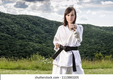 Portrait of female athlete doing karate exercise. Martial arts.