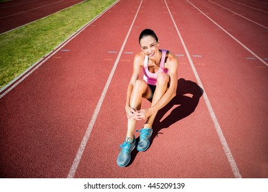 Portrait of female athlete sitting on running track on a sunny day