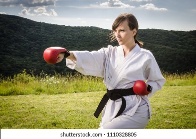 Portrait of female athlete training karate  blows outdoors. Martial arts.
