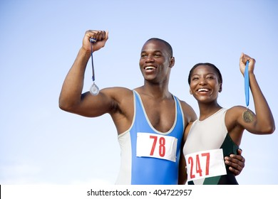 Portrait of a female and athletes with their medals