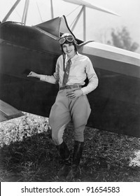Portrait of female aviator with plane