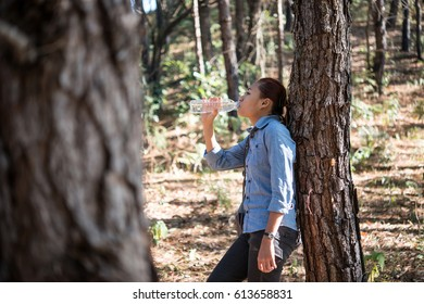 Portrait of female backpacker drinks fresh water from the bottle while carrying backpack in the pine forest.