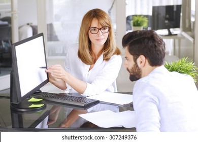 Portrait of female bank employee sitting at desk in front of computer and presenting financial plan to young assistant. Middle age businesswoman points a finger at white screen. Teamwork at office.