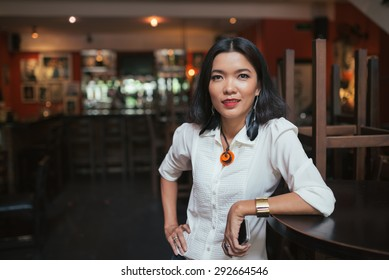 Portrait of female bar manager standing at the table