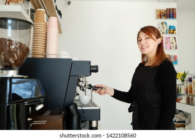 Portrait of female barista using modern beautiful coffee machine with vintage style black and chrome texture design to prepare cappuccino. Macro shot of coffee making equipment. Copy space, background