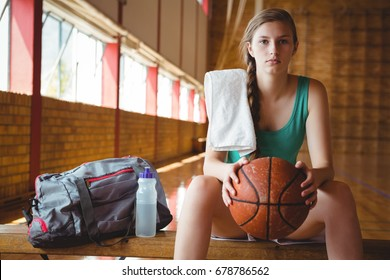 Portrait of female basketball player holding ball while sitting on bench in court