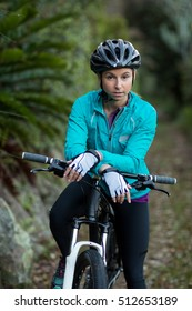Portrait of female biker standing with mountain bike in forest at countryside