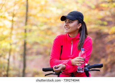 Portrait of female biker standing with mountain bike in forest
