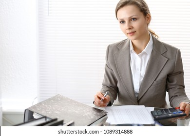 Portrait of female bookkeeper or financial inspector  making report, calculating or checking balance. Copy space area